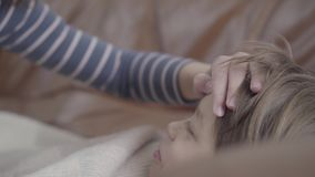 Female hand lying on the forehead of a sick little boy close up. The guy is lying on the bed wrapped in a blanket.  stock footage