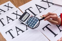 Female hand with magnifier, taxation conception,. Closeup royalty free stock images