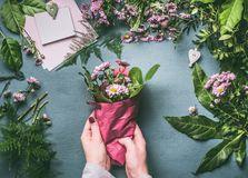 Female hand making beautiful bouquet of pink flowers on florist workspace, top view. Woman wrap bouquet in wrapping paper royalty free stock photography