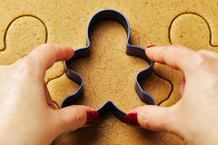 Female hand making christmas gingerbread men cookies Stock Photos