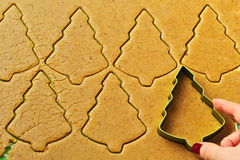 Female hand making christmas tree gingerbread cookies Royalty Free Stock Images