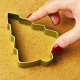 Female hand making christmas tree gingerbread cookies Royalty Free Stock Photography