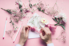 Female Hand making greeting card with envelope with flowers. Wedding, invitation ,Valentine day, Mother`s Day concept. Flat lay Royalty Free Stock Image