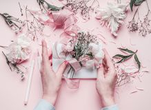 Female hand making greeting card with pastel pink flowers. Top view Royalty Free Stock Photography