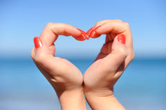 Female hand making a heart shape against Royalty Free Stock Photo