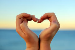Female hand making a heart shape against Royalty Free Stock Image