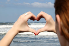 Female hand making a heart shape. Ocean's waves in the background royalty free stock photo