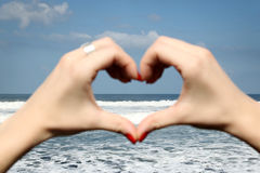 Female hand making a heart shape. Ocean's waves in the background stock photos