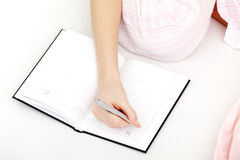 Female hand making notes in callendar Royalty Free Stock Photo
