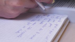Female Hand Making Notes in Notebook While Studying French. Write text in a notebook and read a book on the office desk stock footage