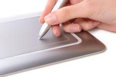 Female hand, making use of pen tablet. Female hand, holding stylus, making use of pen tablet, close-up shot, isolated on white background Royalty Free Stock Photo
