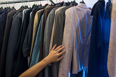 Female hand on male jackets on rack stock photo
