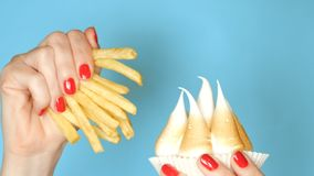 Female hand with a manicure, holding a cupcake with meringue and french fries, on a blue background. close-up stock images