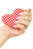 Female hand with manicure. Holding heart on a white background Stock Images