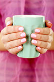Female hand. With manicure holding mint cup Stock Photography