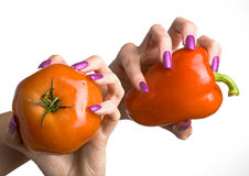 The female hand with manicure holds a tomato and p. The female hand with long nails with manicure holds a tomato and pepper Stock Photos