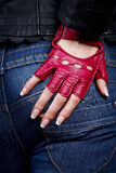 Female hand with manicure in a stylish glove. Female a hand in a stylish glove against jeans Stock Image