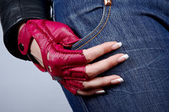 Female hand with manicure in a stylish glove. Female a hand in a stylish glove against jeans Stock Photography