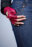 Female hand with manicure in a stylish glove. Female a hand in a stylish glove against jeans Royalty Free Stock Photos