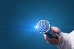 Female hand with microphone . Female hand with microphone on blue background Stock Photo