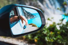 Female hand mirrored in the car side view mirror. Blue mediterranean sea and white rocks in background stock images