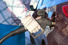 Female hand in mittens refueling car in winter Stock Photography