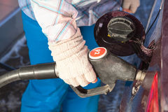 Female hand in mittens refueling vehicle Royalty Free Stock Image