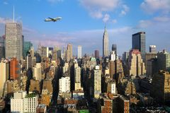 Female hand with mobile phone take picture of midtown of Manhattan. Plane flies over skyscrapers of New York City, Manha Royalty Free Stock Photo