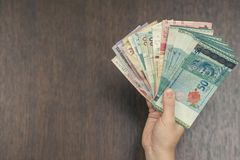 Female hand with money of south-east Asia. Currency of Hong Kong, Indonesia, Malaysia, Thai, Singapore dollar. Travel concept. Stock Photo