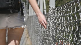 Female hand moving along the surface of grid. Arm of young woman touching metal wire fence. Girl walking during summer stock video footage