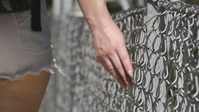 Female hand moving along the surface of grid. Arm of young woman touching metal wire fence. Girl walking during summer stock footage