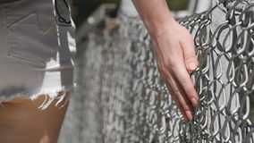 Female hand moving along the surface of grid. Arm of young woman touching metal wire fence. Girl walking during summer stock video
