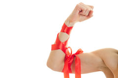 Female hand with muscles wrapped with Red Ribbon close-up Royalty Free Stock Image