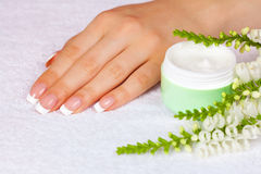 Female hand near jar of cream. Female hand with french manicure near jar of cream on white towel Royalty Free Stock Photography