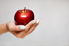 Female Hand Offering an Apple. Female hand offering a red apple Royalty Free Stock Photos