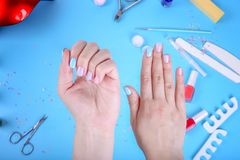 Female hand with ombre manicure on a blue background. Blue manicure with nail polish. Top view stock photo