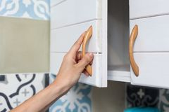 Female hand open the cupboard doors, close up. Female hand open the cupboard doors, close up Stock Photos