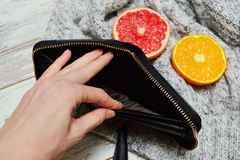 Female hand open empty purse, citrus and a sweater on the background. fashion concept.  stock photography
