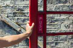 Female hand opening door to phone booth. A young female hand is opening the door of a red phone booth Stock Photo