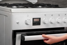 Female hand opening oven in white kitchen gas stove Royalty Free Stock Image