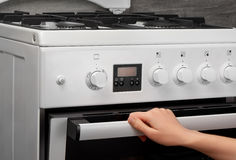 Female hand opening oven in white kitchen gas stove Royalty Free Stock Photography