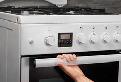 Female hand opening oven in white kitchen gas stove Royalty Free Stock Images