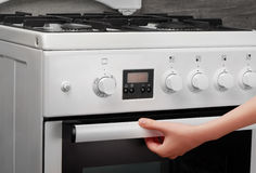 Female hand opening oven in white kitchen stove on gray Royalty Free Stock Images