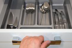 Female hand opens drawer with cutlery. Image royalty free stock photo