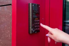 Female hand opens electronic lock by pressing buttons. Security Keyboard Control opens the office. Modern intercom stock images