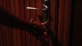 Female hand opens lock on front door by key. Female hand with a bracelet on her wrist opens lock on front door of apartment by key stock footage