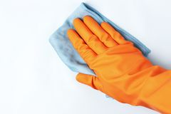 Female hand in orange glove wipes surface with a rag, white background royalty free stock images