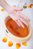 Female hand orange paraffin wax in bowl. Manicure beauty spa salon Royalty Free Stock Photo