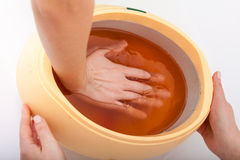 Female hand and orange paraffin wax bowl. Woman in beauty salon Stock Photos
