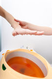 Female hand and orange paraffin wax bowl. Woman in beauty salon Royalty Free Stock Photos
